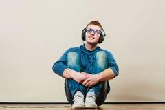 Hombre joven con los auriculares que se sientan en piso Fotos de archivo libres de regalías