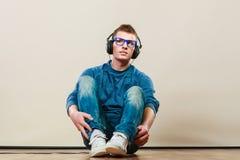 Hombre joven con los auriculares que se sientan en piso Foto de archivo libre de regalías