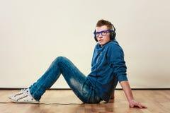 Hombre joven con los auriculares que se sientan en piso Imagen de archivo libre de regalías