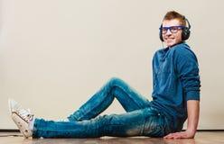 Hombre joven con los auriculares que se sientan en piso Imágenes de archivo libres de regalías