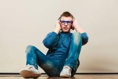 Hombre joven con los auriculares que se sientan en piso Imagen de archivo