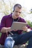 Hombre joven con los auriculares que se sientan, escuchando la música y el holdin Imagen de archivo