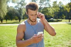 Hombre joven con los auriculares y smartphone en el parque Fotos de archivo