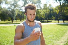 Hombre joven con los auriculares y smartphone en el parque Imagen de archivo libre de regalías