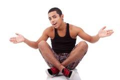 Hombre joven con los brazos abiertos, sentándose en suelo Foto de archivo libre de regalías