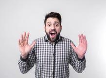 Hombre joven con los brazos levantados La extensión del individuo distribuye Aislado en el fondo blanco Estudiante barbudo que ll Imágenes de archivo libres de regalías