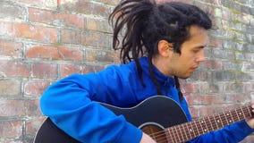 Hombre joven con los dreadlocks que juegan en una guitarra acústica en un fondo de la pared de ladrillo almacen de video