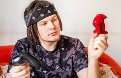 Hombre joven con los dreadlocks que juegan a los videojuegos que miran el regulador del egame del th que se sienta en un sofá ana Fotos de archivo