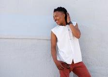 Hombre joven con los dreadlocks que sonríe afuera contra la pared gris Imagen de archivo