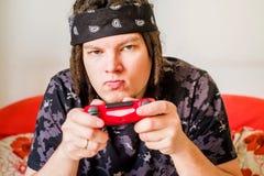 Hombre joven con los dreadlocks y la cara seria que juegan a los videojuegos con una palanca de mando que se sienta en un sofá an Foto de archivo