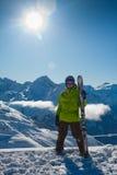 Hombre joven con los esquís Imagenes de archivo