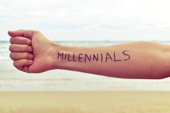 Hombre joven con los millennials de la palabra escritos en su brazo Imagen de archivo