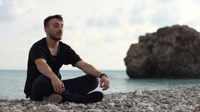 Hombre joven con los ojos cerrados que se sientan y que se relajan en estilo de la yoga cerca de vista lateral de mar que sorpren almacen de video