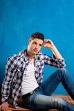 Hombre joven con los pantalones vaqueros del dril de algodón de la camisa de tela escocesa en azul Imagen de archivo