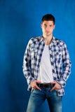 Hombre joven con los pantalones vaqueros del dril de algodón de la camisa de tela escocesa en azul Fotografía de archivo libre de regalías