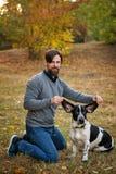 Hombre joven con los paseos del perro en parque del otoño imagen de archivo libre de regalías