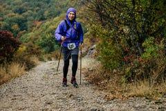 Hombre joven con los polos que caminan que corren en tiempo lluvioso en rastro de montaña Foto de archivo