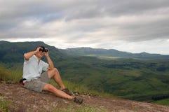 Hombre joven con los prismáticos Foto de archivo libre de regalías