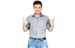 Hombre joven con los pulgares para arriba en el fondo blanco Imagenes de archivo
