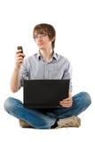 Hombre joven con los sms de la computadora portátil y de la escritura fotografía de archivo libre de regalías