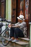 Hombre joven con los tatuajes que se sientan cerca de la puerta del estudio del tatuaje Imagen de archivo