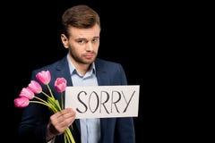 Hombre joven con los tulipanes y la muestra triste que miran la cámara Fotografía de archivo