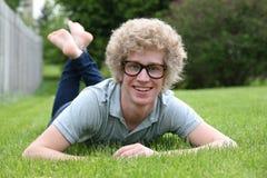 Hombre joven con los vidrios nerdy que ponen en el estómago Fotos de archivo