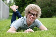 Hombre joven con los vidrios nerdy que ponen en el estómago Imagen de archivo libre de regalías
