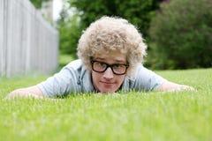 Hombre joven con los vidrios nerdy que ponen en el estómago Fotografía de archivo libre de regalías