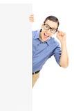 Hombre joven con los vidrios que se colocan detrás del panel en blanco Foto de archivo libre de regalías