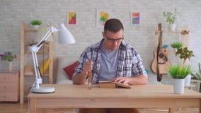 Hombre joven con los vidrios con un rosario en sus manos y la lectura de la biblia metrajes