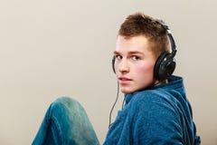 Hombre joven con música que escucha de los auriculares Foto de archivo