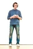 Hombre joven con música que escucha de los auriculares Foto de archivo libre de regalías