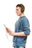 Hombre joven con música que escucha de los auriculares Fotografía de archivo