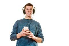 Hombre joven con música que escucha de los auriculares Imágenes de archivo libres de regalías