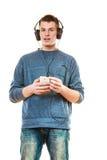 Hombre joven con música que escucha de los auriculares Fotos de archivo libres de regalías