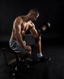 Hombre joven con pesas de gimnasia de elevación del pecho desnudo Fotografía de archivo