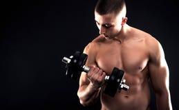 Hombre joven con pesas de gimnasia de elevación del pecho desnudo Imagenes de archivo