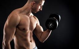 Hombre joven con pesas de gimnasia de elevación del pecho desnudo Foto de archivo