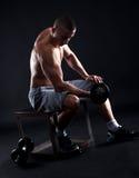 Hombre joven con pesas de gimnasia de elevación del pecho desnudo Foto de archivo libre de regalías