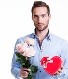 Hombre joven con rosas rosadas y un regalo. Imagen de archivo libre de regalías