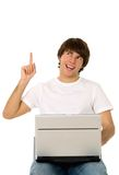 Hombre joven con señalar de la computadora portátil Foto de archivo libre de regalías