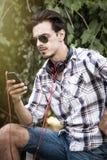 Hombre joven con smartphone de las gafas de sol y el puerto al aire libre de los auriculares imágenes de archivo libres de regalías