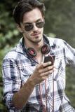 Hombre joven con smartphone de las gafas de sol y el puerto al aire libre de los auriculares fotos de archivo