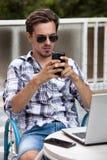 Hombre joven con smartphone de las gafas de sol y ordenador portátil al aire libre imagen de archivo libre de regalías