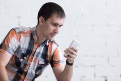 Hombre joven con smartphone dentro Fotos de archivo libres de regalías