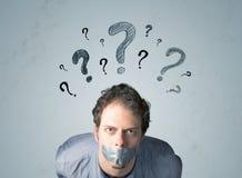 Hombre joven con símbolos pegados del signo de la boca y de interrogación Foto de archivo