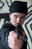 Hombre joven con un arma Imagenes de archivo