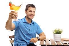 Hombre joven con un cóctel que se sienta en una tabla Imagenes de archivo