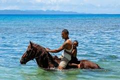 Hombre joven con un caballo de montar a caballo del muchacho en la playa en la isla de Taveuni Foto de archivo